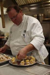 Annie Gunn's & Smokehouse MarketChef Lou Rook preps Shaved Wine Barrel-Smoked Turkey with Baetje Farms Miette on County Line Farms Sweet Potato Biscuits